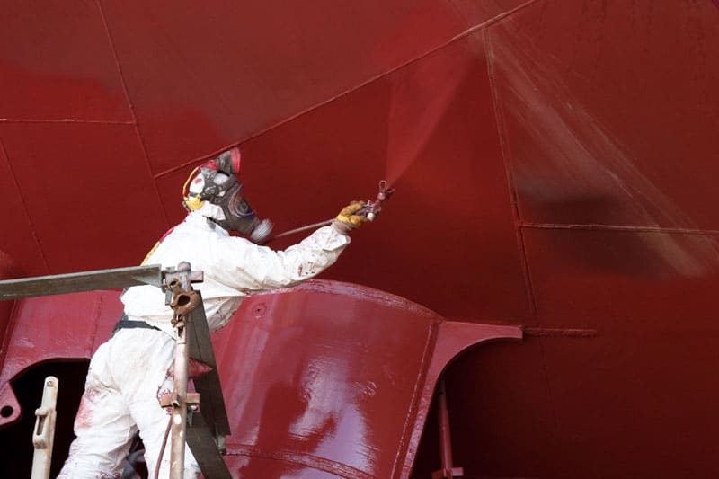 Liquid coating being applied to large, red surface